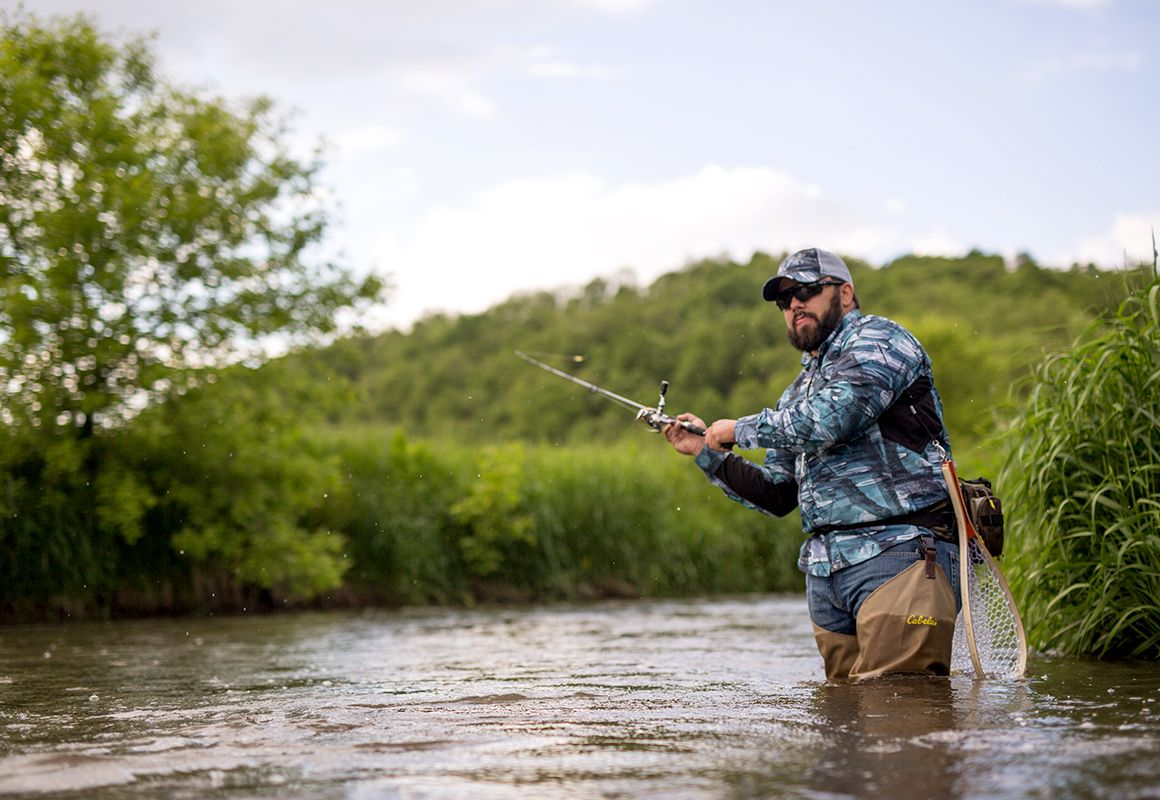 Fly fisherman using the onX Hunt app for finding river