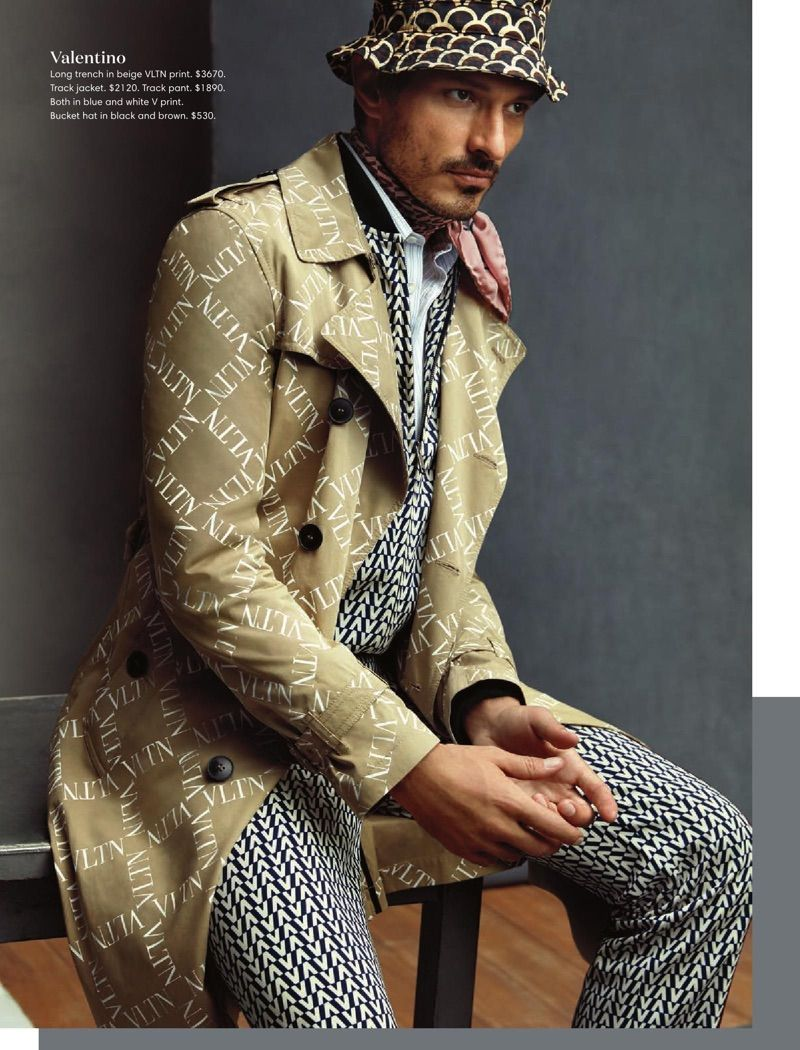 2203c086 Making a printed statement, Andres Velencoso wears a Valentino logo print  trench coat, track suit, and bucket hat.