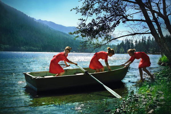 """The Escape    """"This is made from three images, shot at Lake Crescent in the Olympic Peninsula, near Seattle. My partner and I shot images of me moving to and from the boat, keeping thecamera in one position for most of them. I composited them in Photoshop to produce a surreal, multi-self image of the scene."""""""