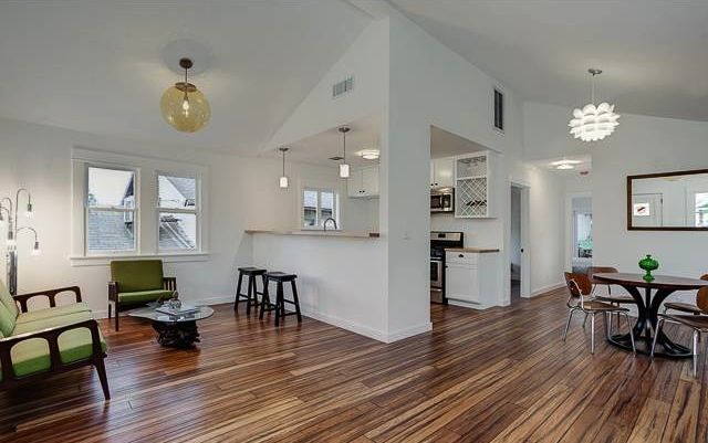 Living Room With Open Floor Plan Vaulted Ceiling And Wood Floors