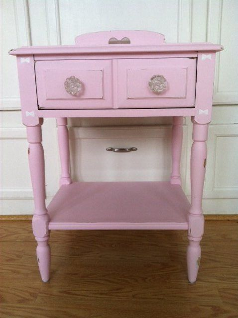 "Custom refinished bedside table by ""PicksNFinds4U"". This table has been refurbished and then repainted and hand distressed. The color is a soft and striking ""Pink Lace"" by Benjamin Moore Paints in an eggshell  finish. I've replaced the old tired drawer pulls with lovely frosted glass rose knobs. The perfect touch for this table drawer. The inside of the drawer bottom has been painted pink and the inside sides of the drawer have been painted white.  The table has been lightly ..."