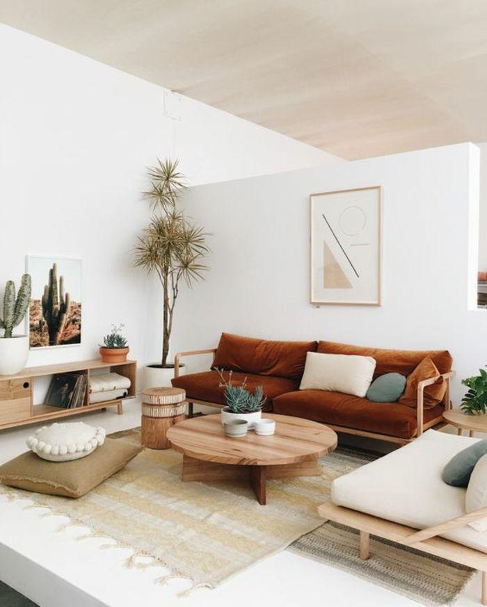 braune Polstercouch und weißer Sessel, runder Couchtisch aus Holz ...