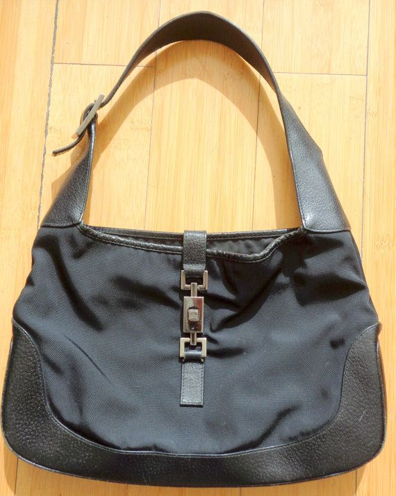 Vintage Jackie O Black Nylon Bag with Leather Trim. The Hardware is Silvertone. The Dust Cover is fine. I found it doing laundry!