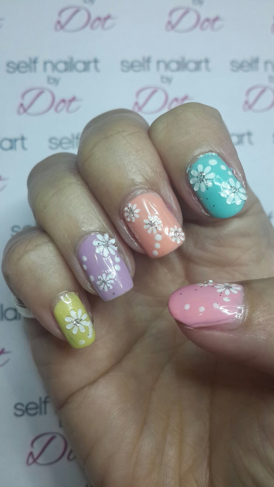 Pastel colored nails with floral decal nailart