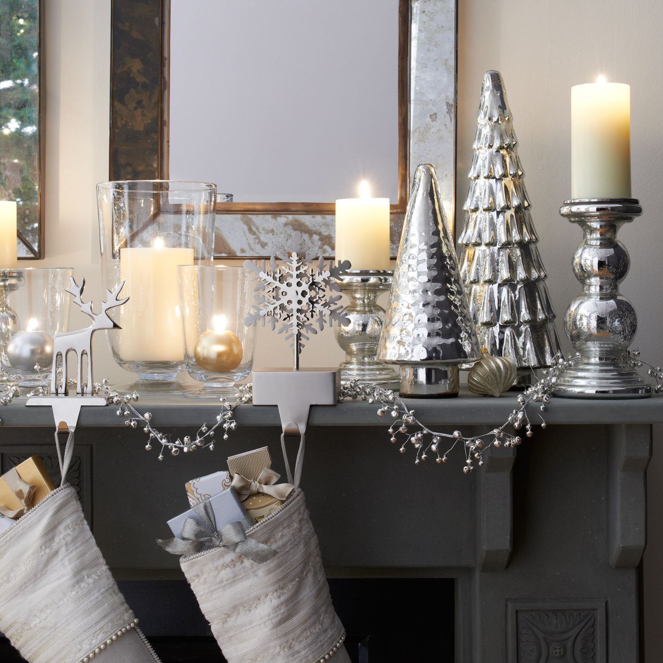 Create a vintage-style wonderland of shimmering elegance lit by classic mercury glass pillar holders and antiqued glass trees that glow from within (thanks to concealed batteries). Swag a delicate silver beaded garland between stockings hung with care from silver reindeer and snowflakes. Above it all, a row of square mirrors framed in distressed tin reflects the glimmer and shine.