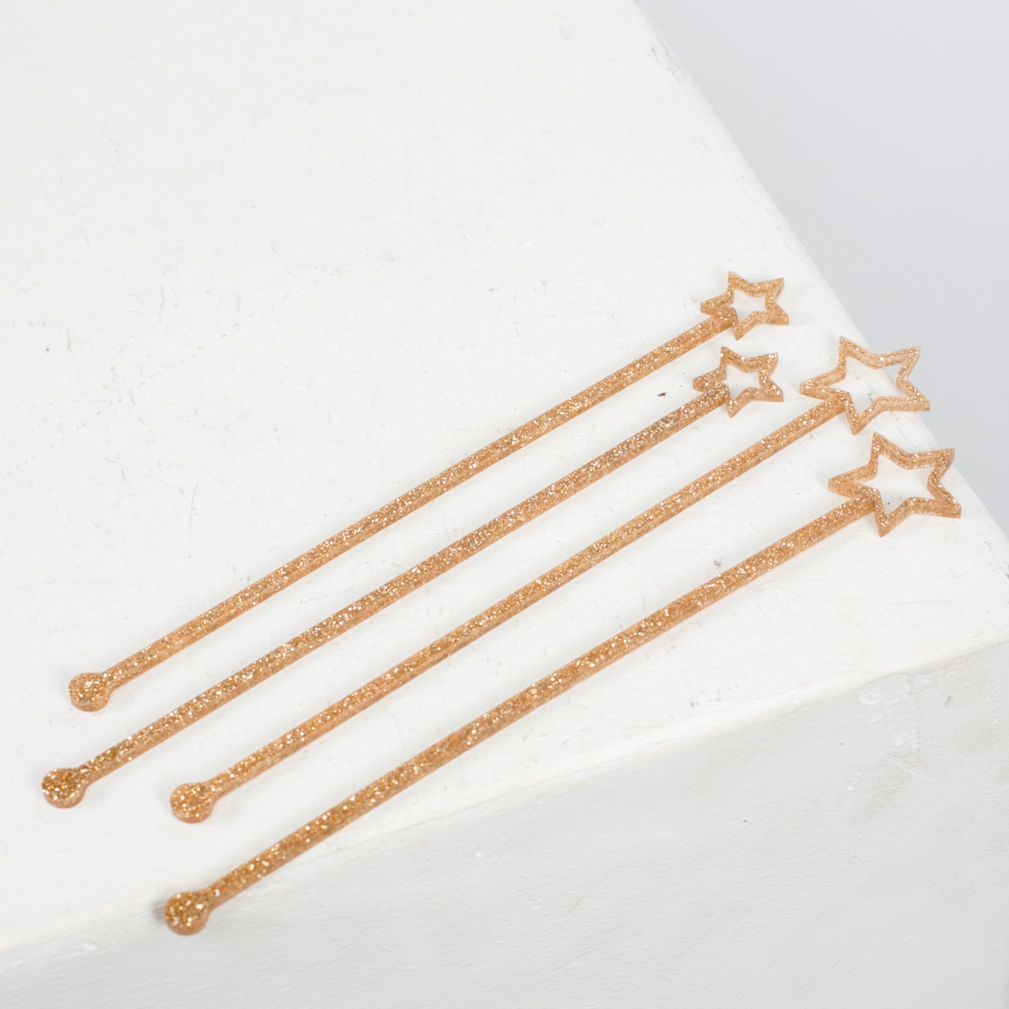 Gold Glitter Swizzle Sticks by Meri Meri. Every occasion could use a bit of gold. These swizzle sticks can help mix any drink, each is decorated with a gold glittered star. Measures 8