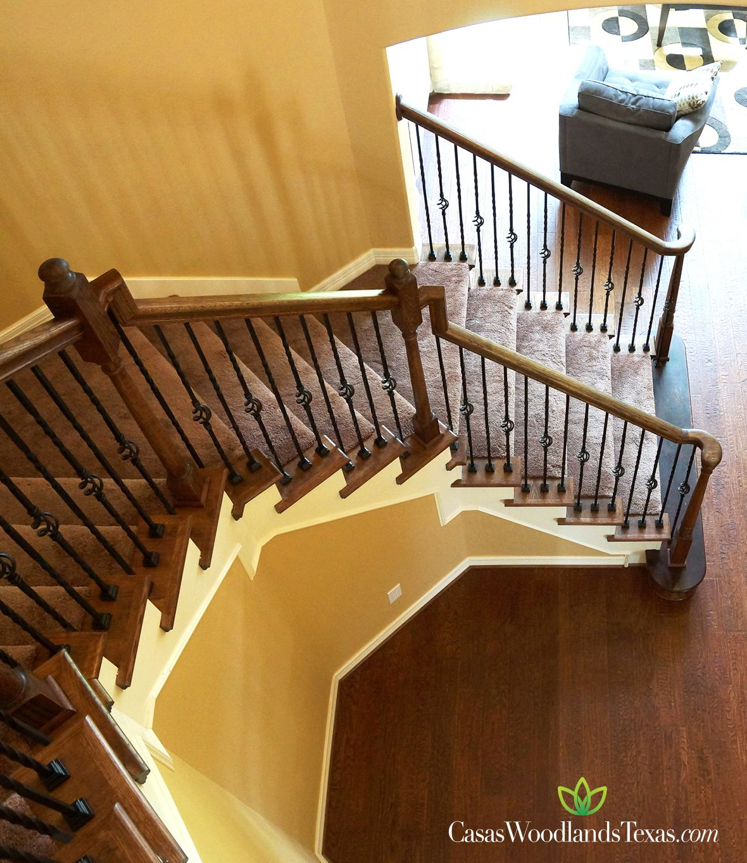 Las escaleras cuentan con un elegante barandal de madera y for Escaleras interiores de hierro