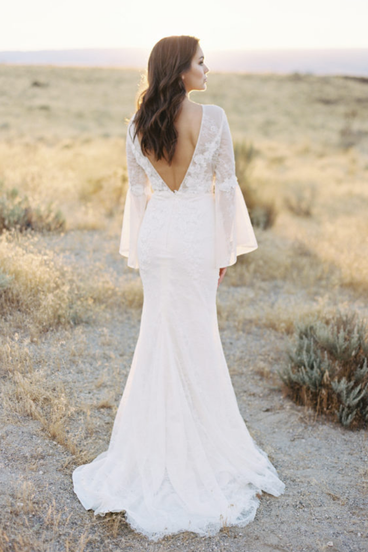 A modern boho wedding gown with a low back vneck and sheer bell