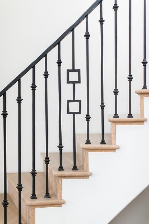 Gorgeous Wood And Iron Staircase Boasts Mixed Iron Spindles Complementing  An Iron Handrail And Light Wood Treads.