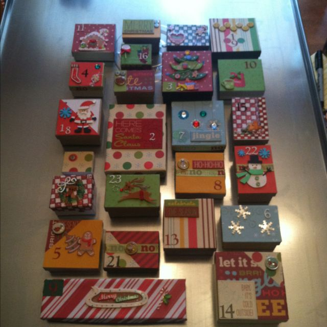 This is the advent calendar I made using old jewelry boxes and scrapbook paper. I did have to buy stickers and embellishments and the oil drip pan that the boxes are stuck to using magnets. I am filling the boxes with candy and bible verses regarding the birth of Jesus.