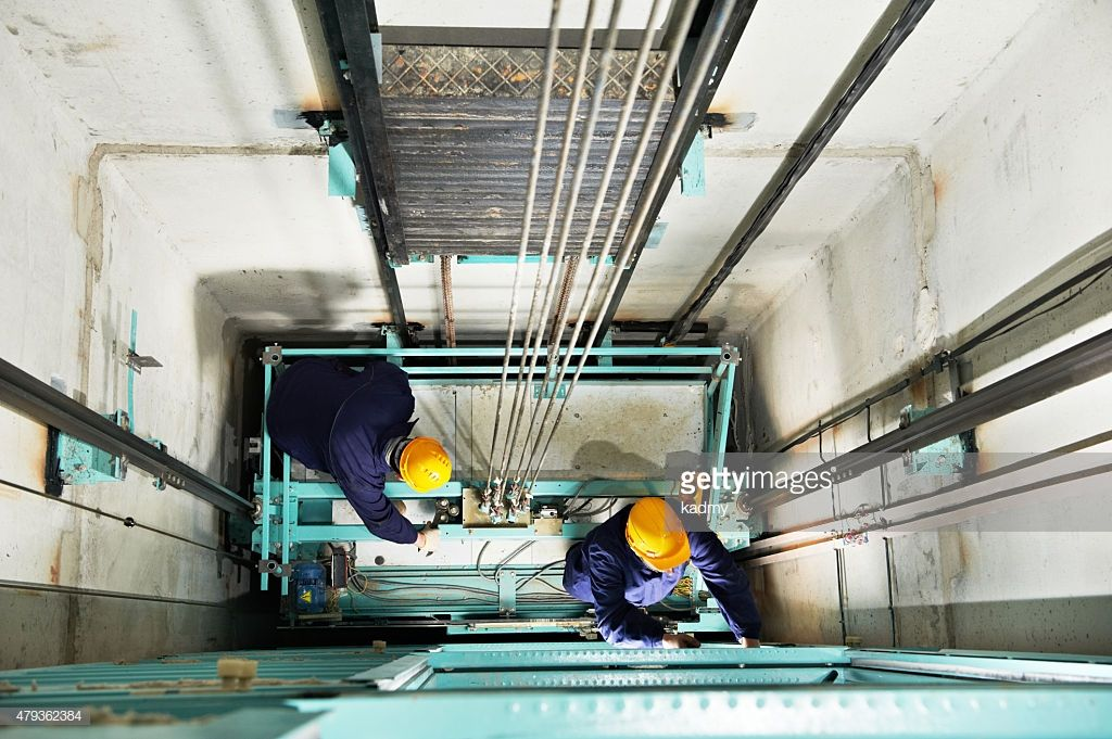 two male technician machinist worker at work adjusting