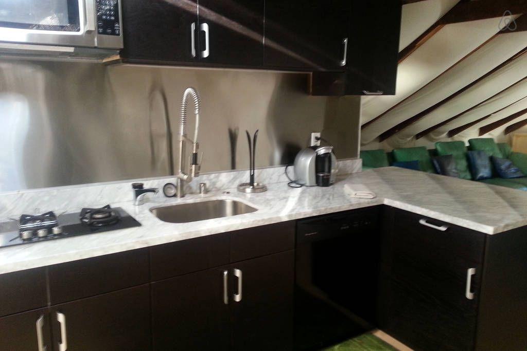 3 burners, a microwave, stainless steel sink, backsplash