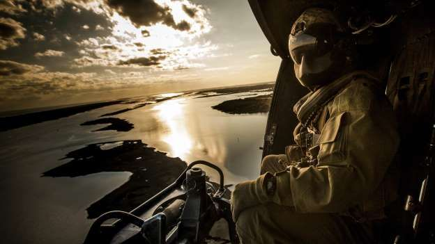 Slide 20 of 33: A Crew Chief assigned to Marine Light Attack Helicopter Squadron 167 observes the landing zone from a UH-1Y Huey during a training operation at Marine Corps Auxiliary Landing Field Bogue, North Carolina, on March 9, 2017.