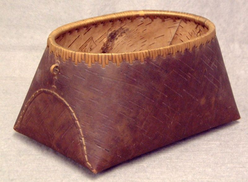 Birch Bark Basket, circa 1870 - Made by Samuel Benedict (1837 -?) - This birch bark basket was made ca. 1870 by Indian guide Samuel Benedict of Lake George and Indian Lake, New York. It measures 5 inches high by 10 inches by 6 inches. This small basket is made from a single piece of birch bark that has been cut, bent, and sewn into a watertight vessel. It has a flat, rectangular bottom and oval mouth. Small loops are attached at each end near the rim of the basket, probably for a missing…
