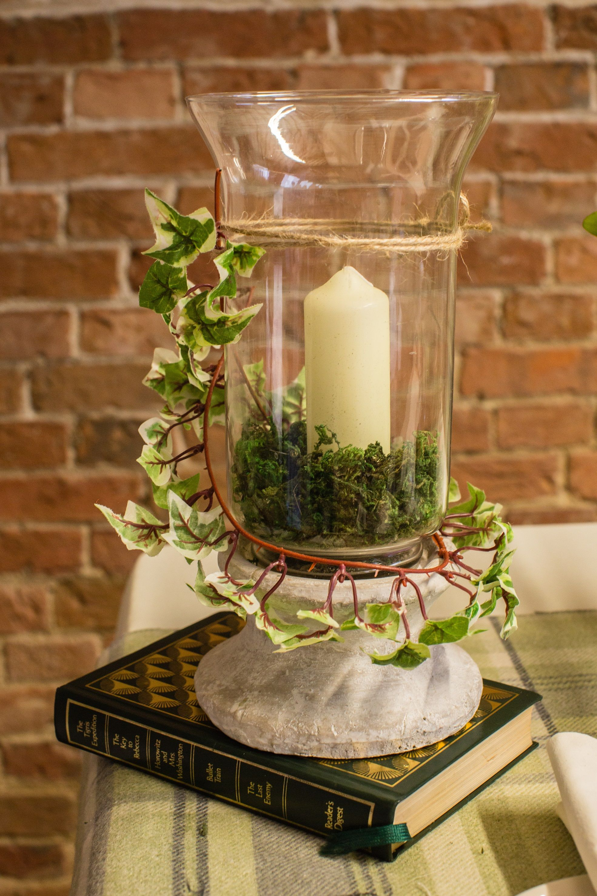 Ivy Wrapped Around A Stone Based Hurricane Vase, Filled With Moss And A  Pillar Candle