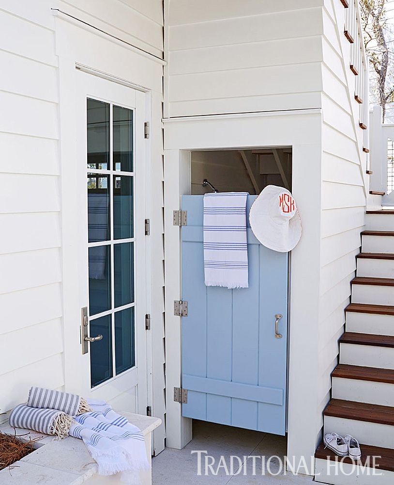 behind the blue door, an outdoor shower—a beach house necessity—is
