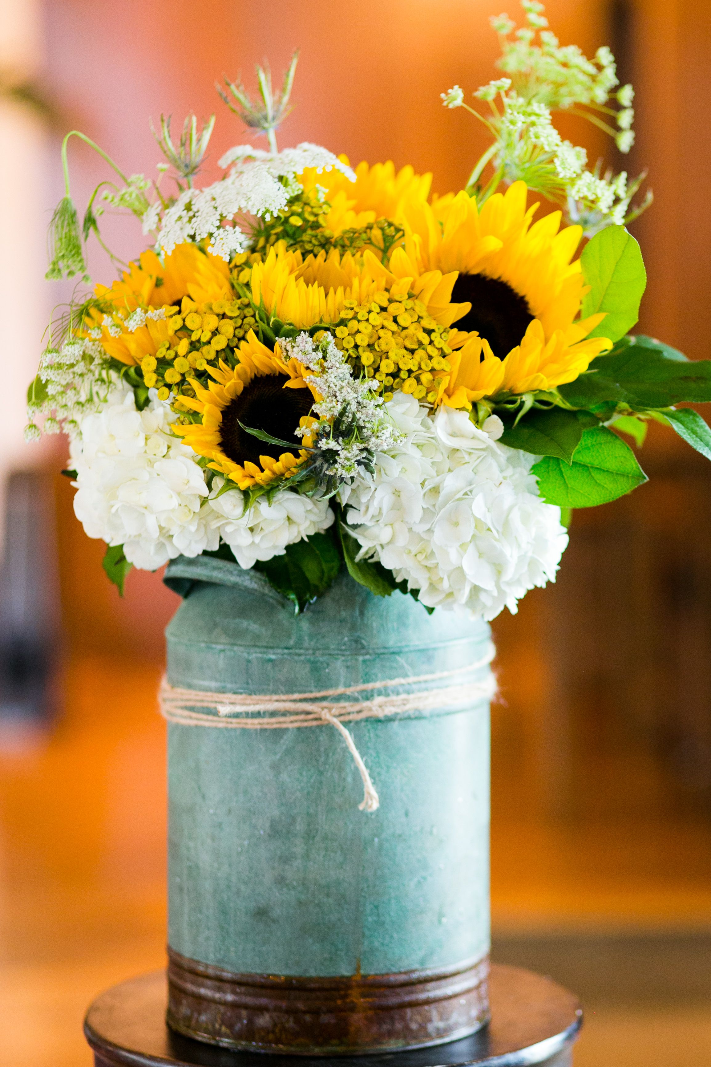 A Loosely Constructed Arrangement Of White Hydrangea, Yellow Sunflowers, Yarrow,