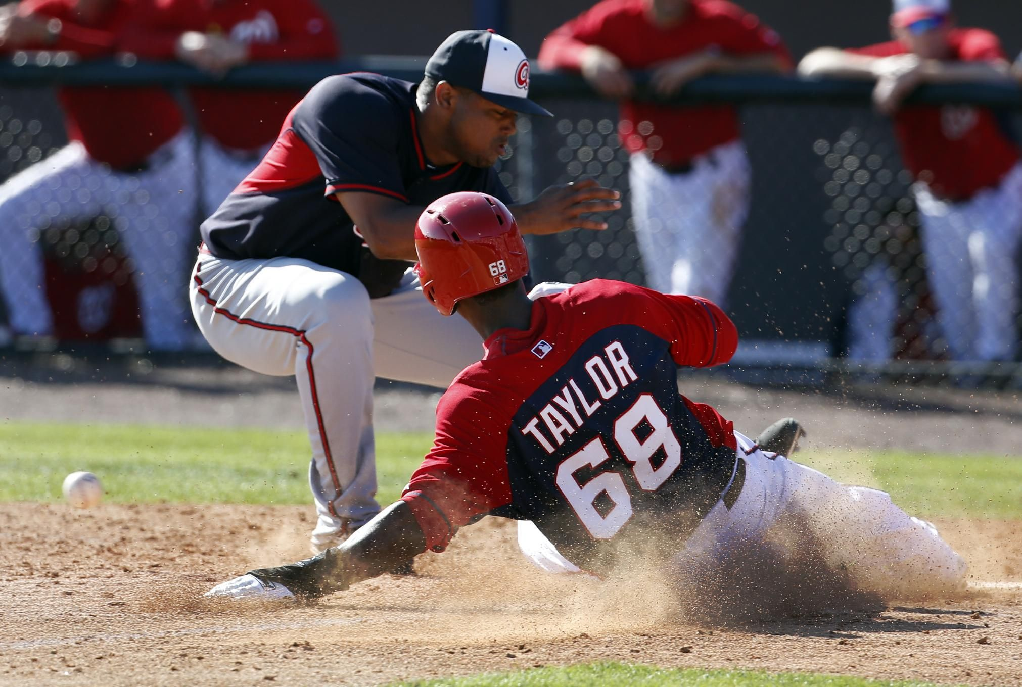 Washington Nationals' Michael Taylor slides safely into home as Atlanta Braves relief pitcher Juan Jaime can't handle throw after a passed ball, in the fifth inning of an exhibition baseball game, Saturday, March 1, 2014, in Viera, Fla. The Nationals won 16-15. (AP Photo/Alex Brandon)