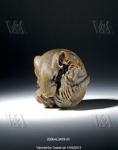 Netsuke figure of a rat coiled into a ball. Carved wood. Japan, 19th century.