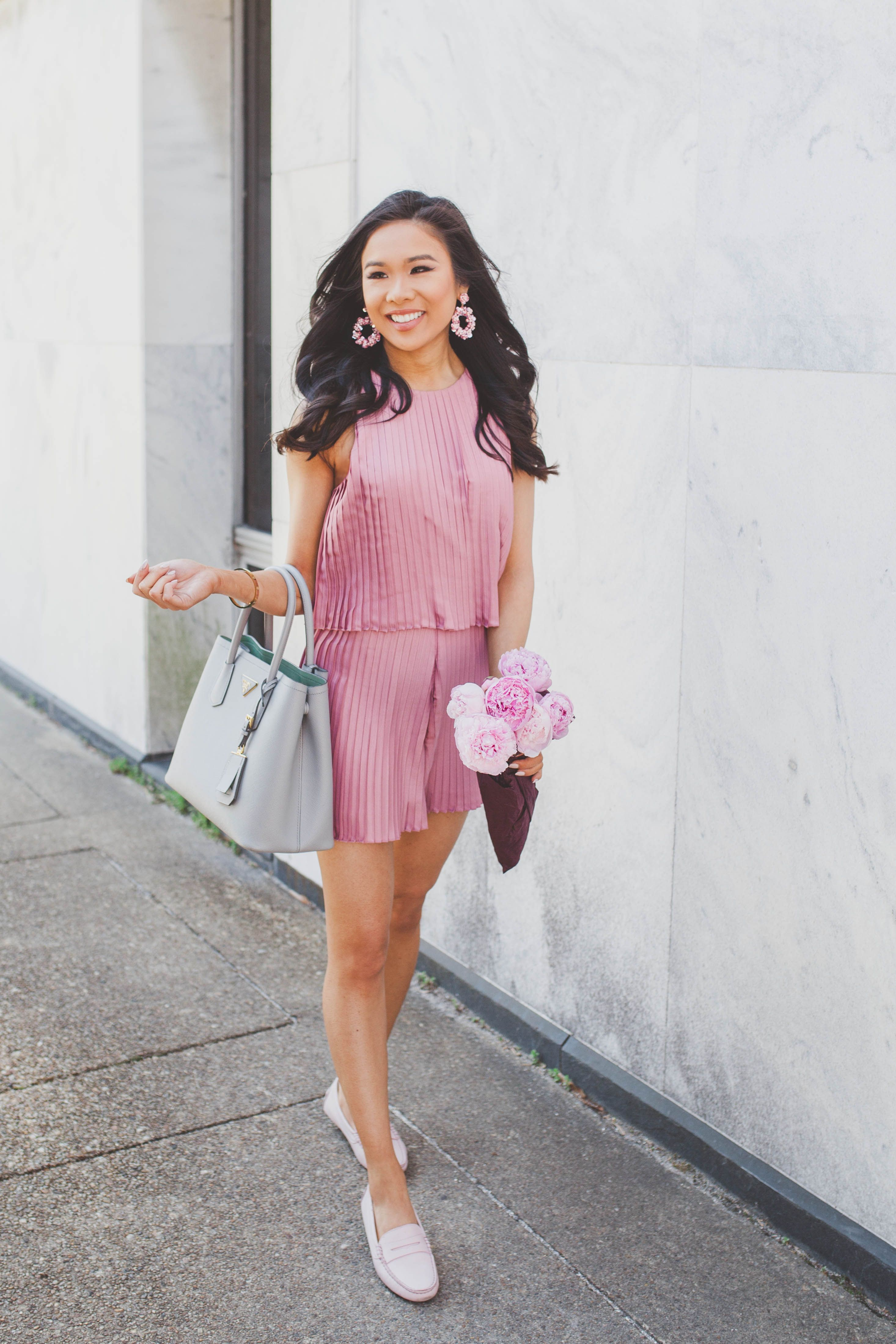 c3b5f189e237 Blogger Hoang-Kim wears a pink pleated romper with blush penny drivers and  pink peonies