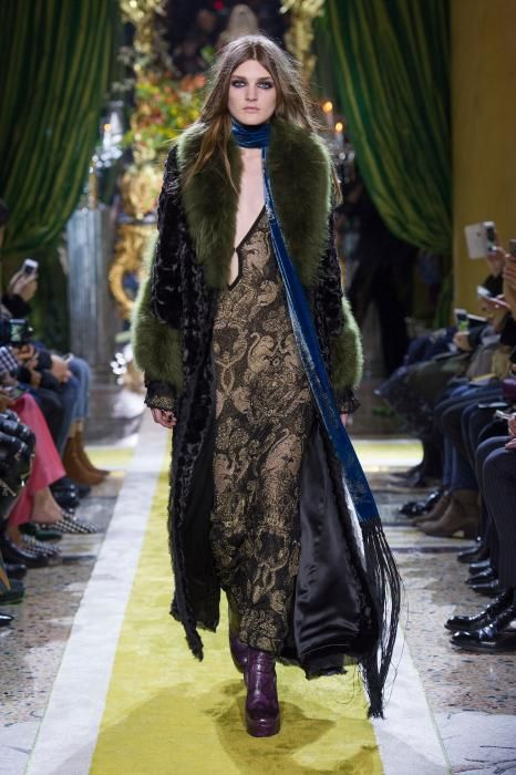 A female model wearing a sheer, fully embroidered, black and gold dress, under a dark blue velvet coat, with a green fur cuffs and collar, and purple python print high-heel boots