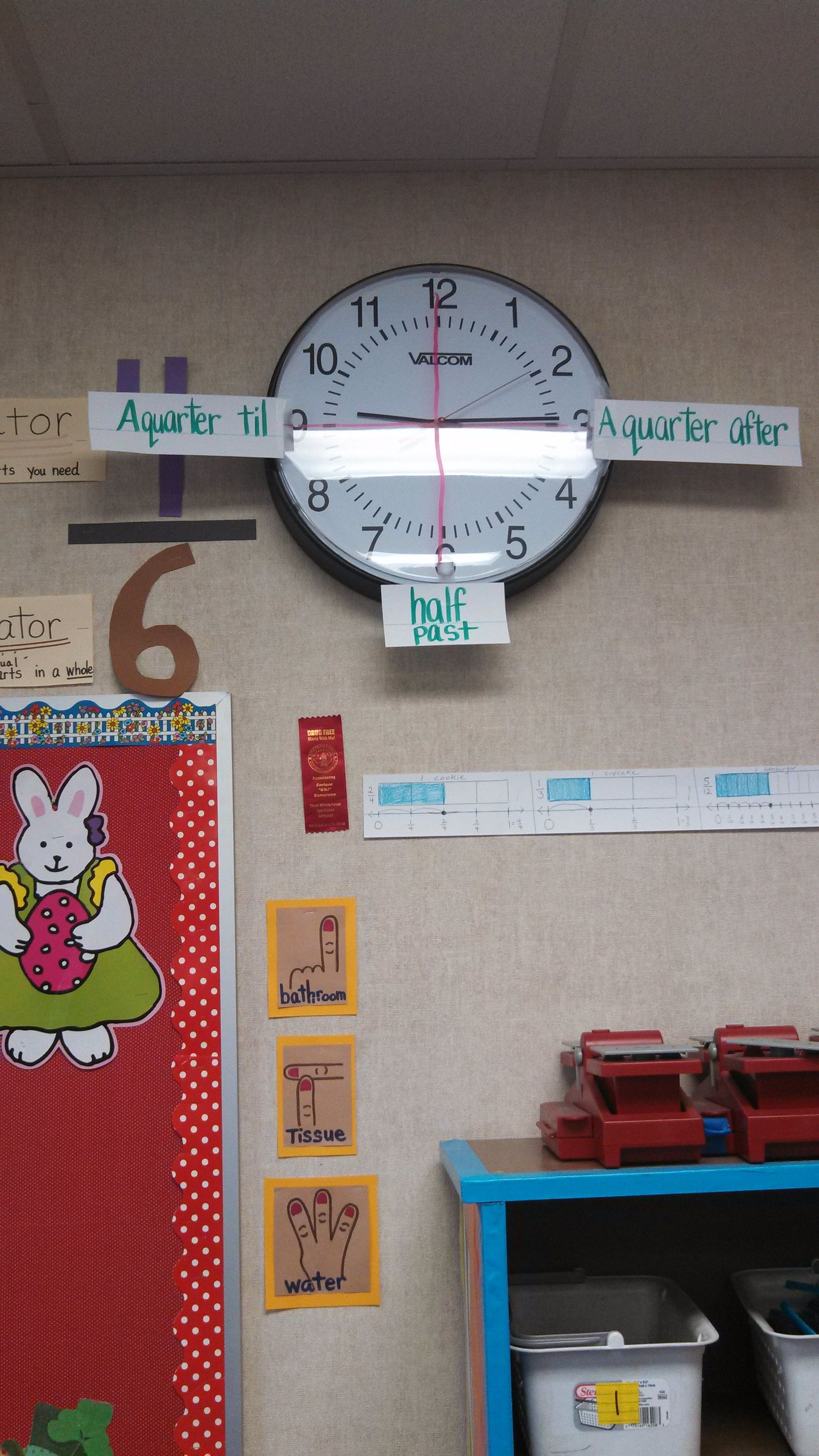 """This clock has the main time """"checkpoints"""" labeled on it: a quarter til, half past, and a quarter after. This would be a great thing to label on your classroom clock in order to help the students learn about time and how to tell time. I would definitely have this in my classroom for a third grade level. Having it posted on the clock high on the wall would allow any student to look at the clock at any given time for help. 5159"""
