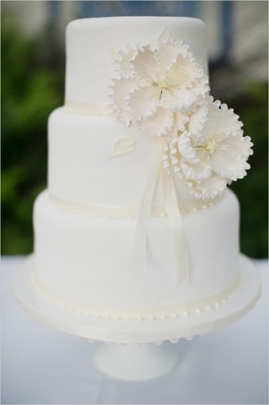 white wedding cake with floral accent #weddingcake #whiteweddingcake #weddingchicks http://www.weddingchicks.com/2014/02/11/relaxed-california-wedding/