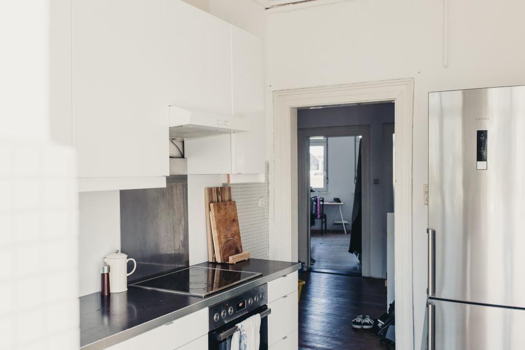 Schöne, helle Altbauküche mit dunklem Holzboden und weißen Möbeln ...