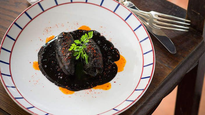 Stuffed squid in black ink sauce (encornets farcis à l'encre de seiche) | Located on the French coast, Biarritz cuisine includes many seafood dishes. This recipe for stuffed squid also features the famous Bayonne ham, a signature delicacy from the region.
