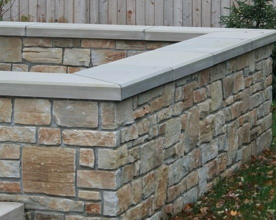 A Block Wall Covered With Natural Stone Veneer Natural Stone Retaining Wall Brick Veneer Wall Stone Decor