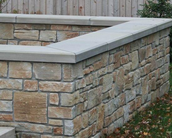 A Block Wall Covered With Natural Stone Veneer Natural Stone Retaining Wall Brick Veneer Wall Stone Veneer Wall