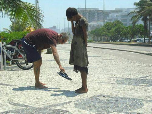 A man giving his shoes to a poor homeless young girl