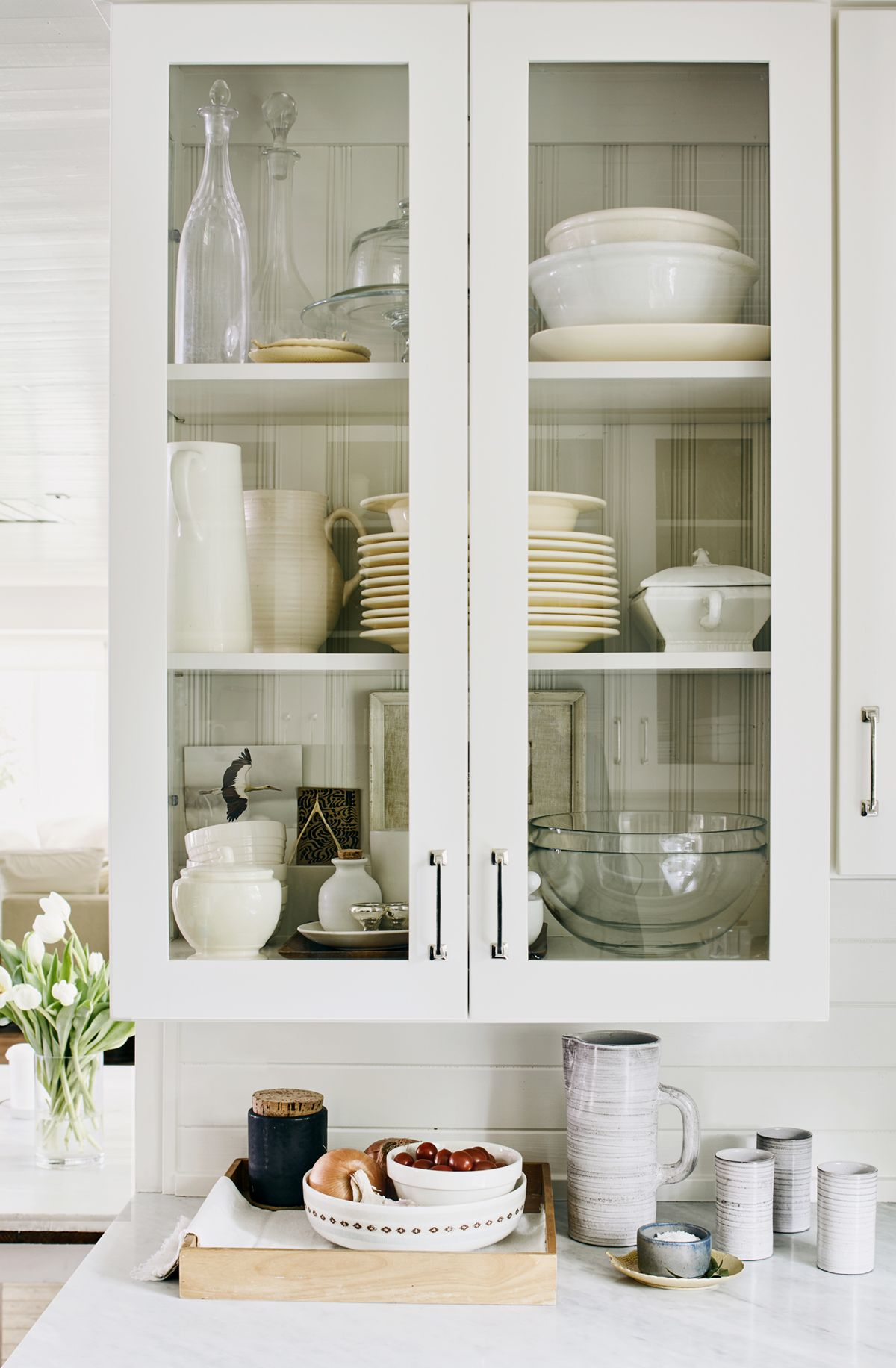 classic white glassfront cabinets show off collections in the ...