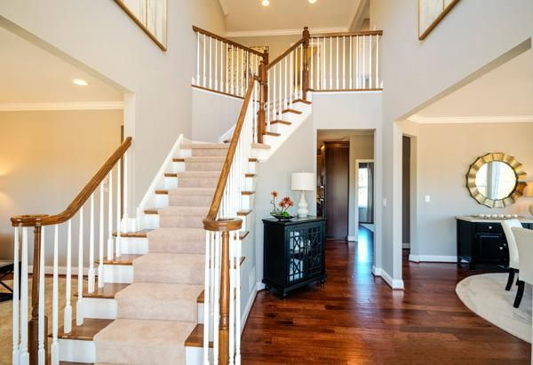 Gleaming Wood Floors Define This Elegant Foyer With A Sweeping