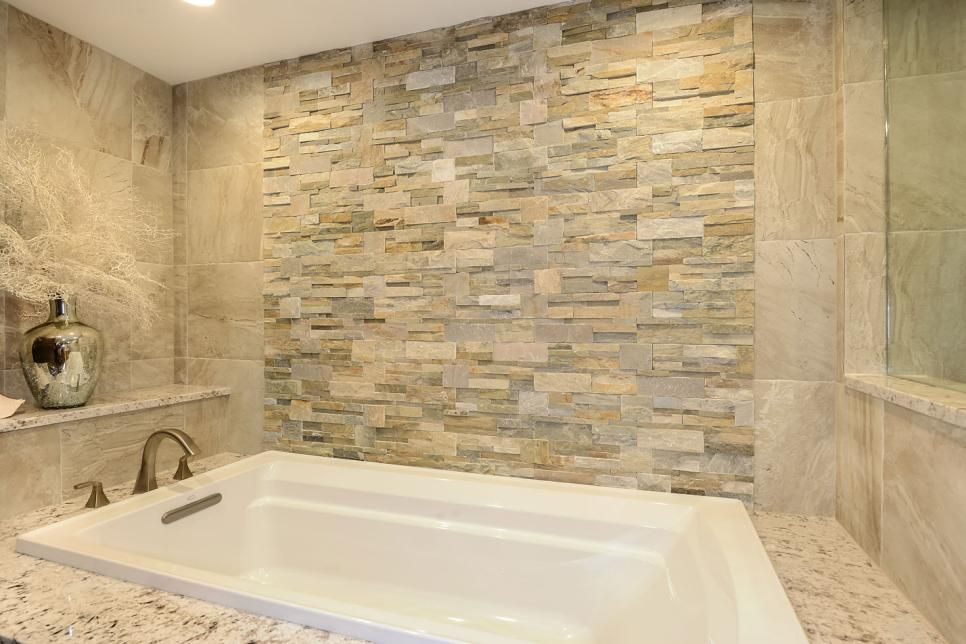Delicieux This Master Bathroom Remodel Features A Drop In Bathtub With A Natural  Stone Accent Wall In Various Neutral Tones. Large, Square Neutral Tiles  Cover The ...