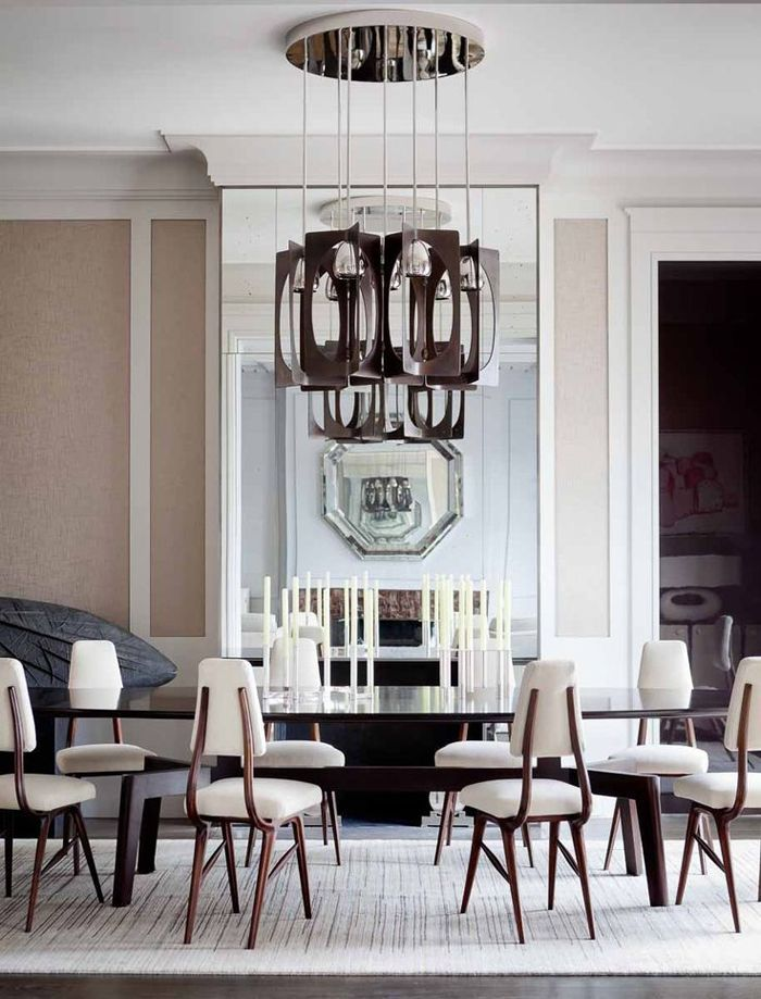 So French dining room set designed by Jean-Louis Deniot. Photo by Jérôme Galland. The glass and wooden oval dining table works perfectly with the contemporary dining chairs in a contrast with the high ceilings tipical of Haussman buildings.