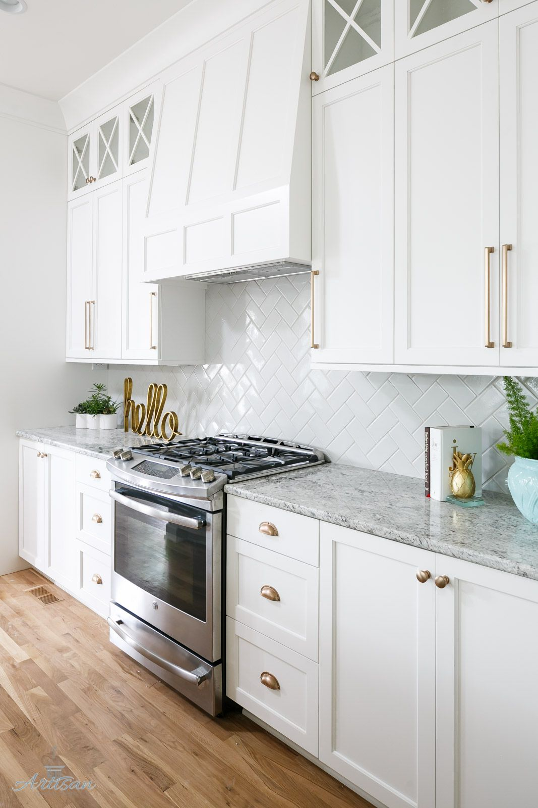 White kitchen design with marble countertops and gold