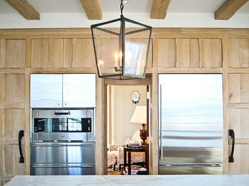 Rustic kitchen cabinets in fumed white oak or plank white pine, paired here with modern stainless appliances, wrought iron handles, lantern lights.  - Bates Corkern Studio