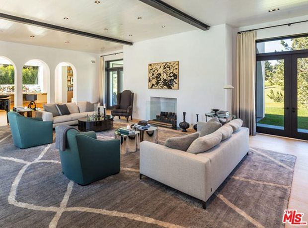 Lori Loughlin's living room features extra wide plank floorboards, a minimalist fireplace and wood beams on the ceiling.