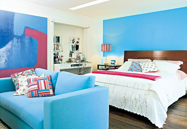 Extremamente relaxante, o turquesa dita esta ambientação. O ponto de partida para o projeto foi a pintura da parede atrás da cama. Na sala íntima, o sofá tem a mesma tonalidade. O rosa surge nas almofadas e na roupa de cama
