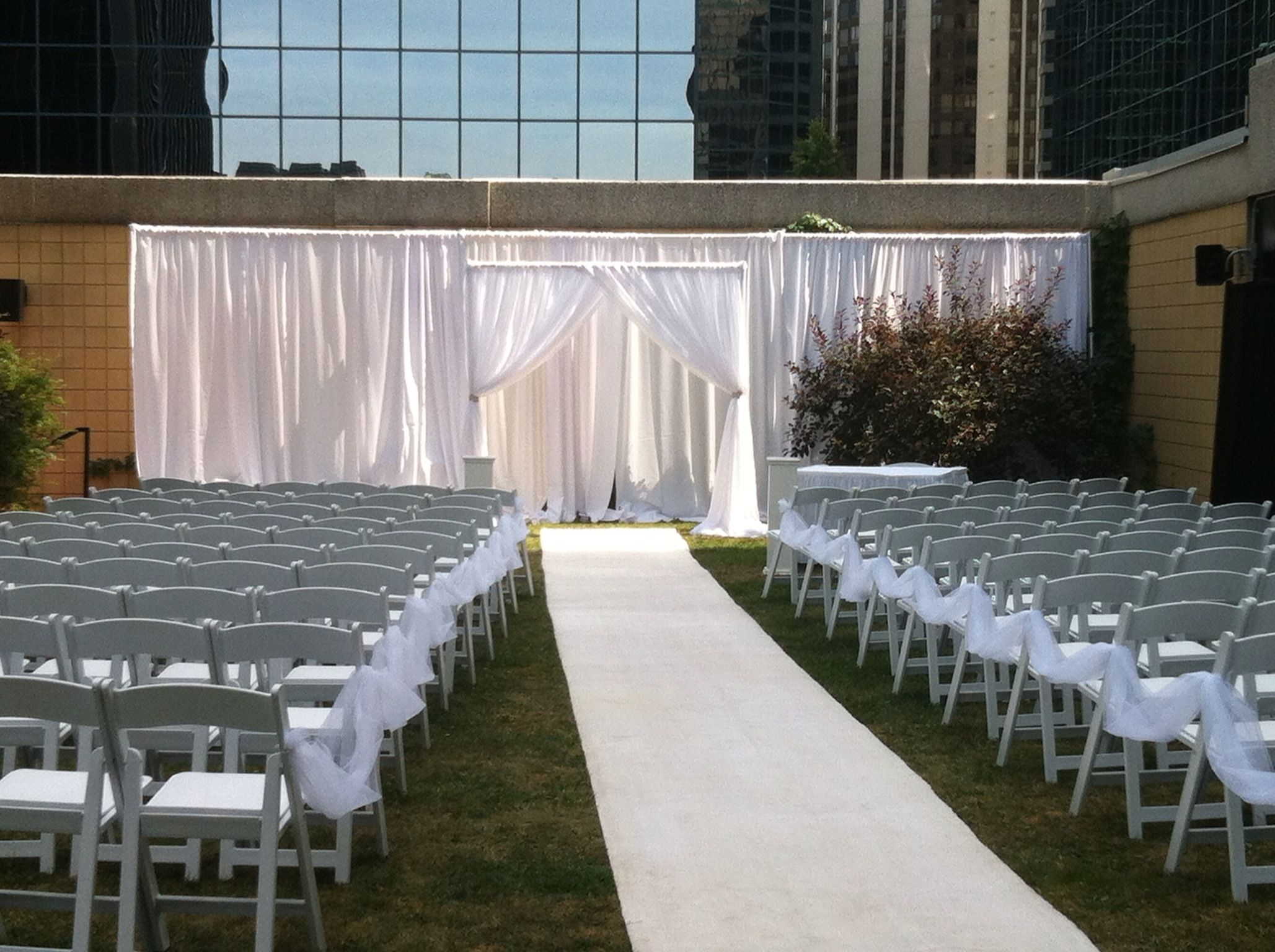 Outside ceremony. Flowing white fabric dresses up a plain garden wall