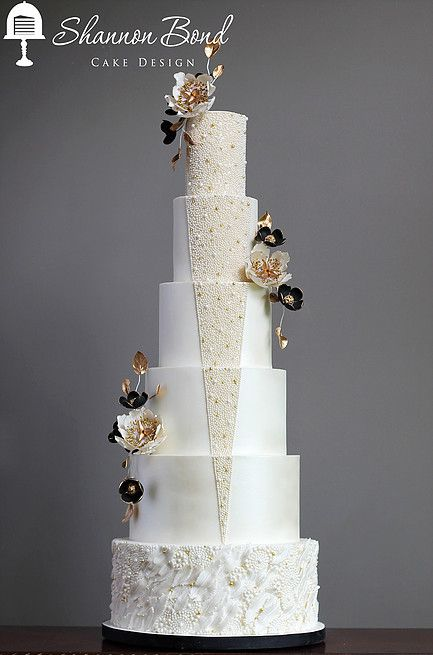 Gatsby Wedding Cake. 1920's inspired wedding cake designed by Shannon Bond Cake Design. www.sbcakedesign.com. Hand cut feathers and geometric placed pearls with gold, white and black sugar flowers.