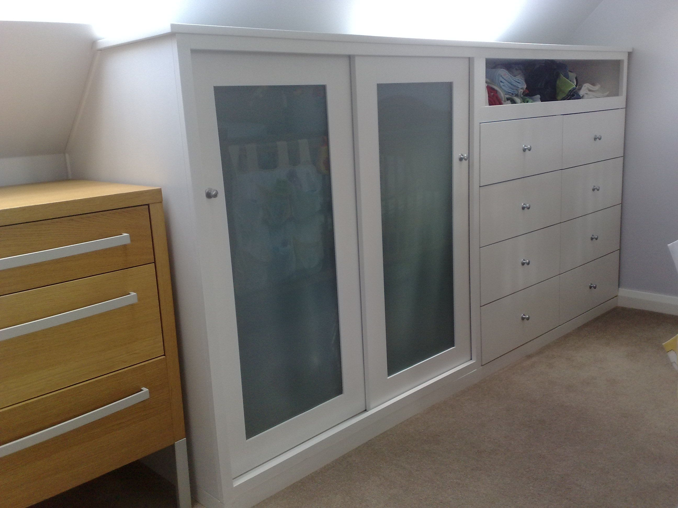 A Half Wardrobe With Drawers Designed To Fit Under An Eave