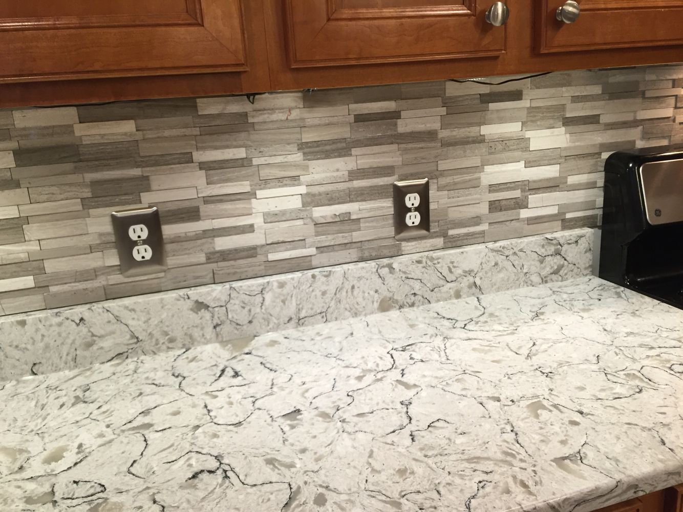 Gray Subway Mosaic Wall Tiles On Spring Valley Quartz Countertops.