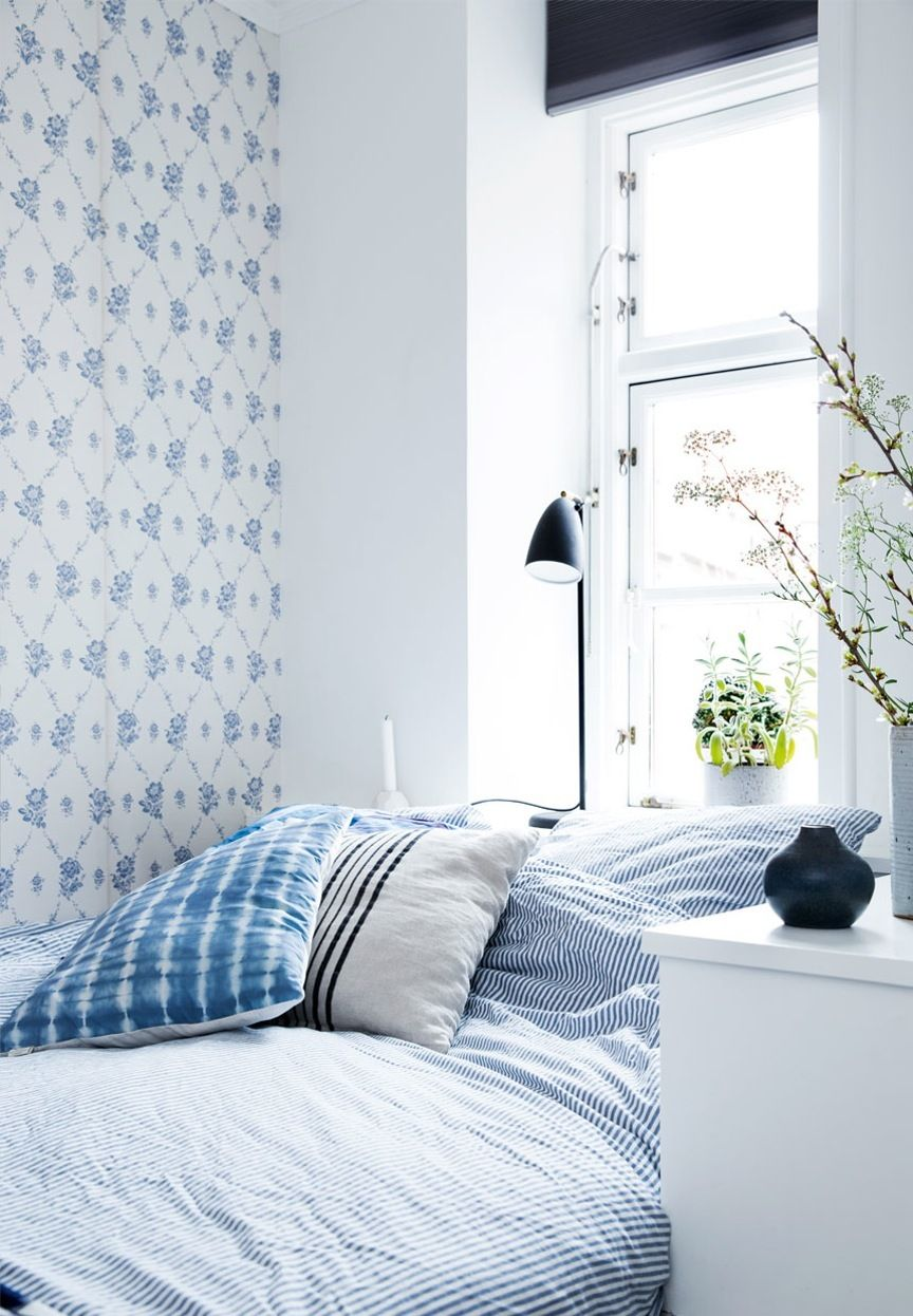 Bright bedroom in blue tones featuring green plants