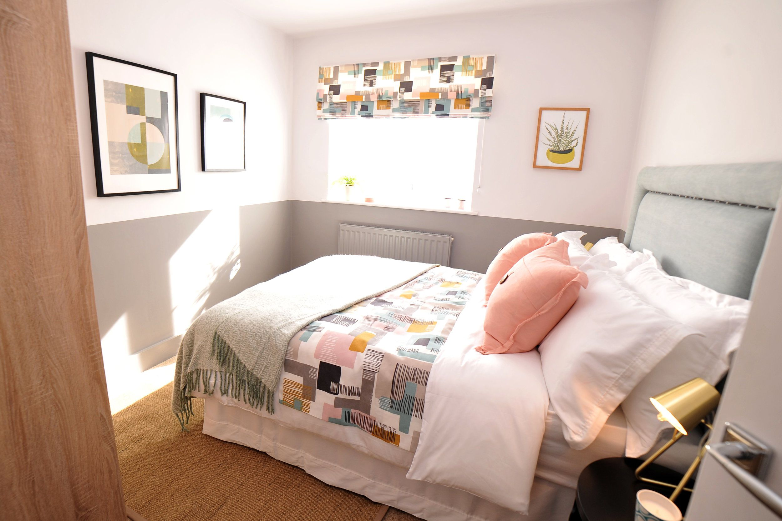 Bright guest bedroom with grey half height painted walls