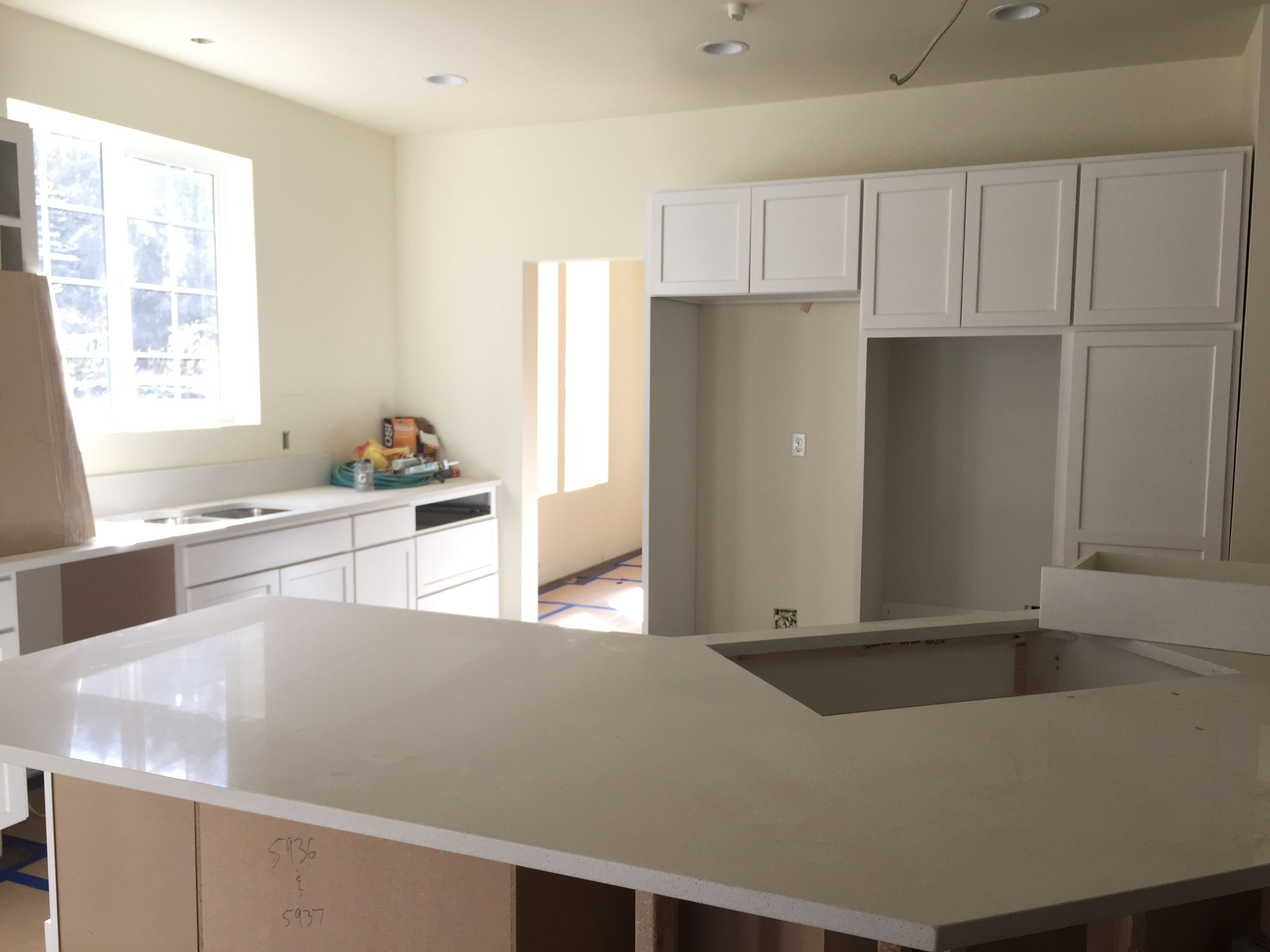 White painted kitchen cabinets and Frost White quartz ...