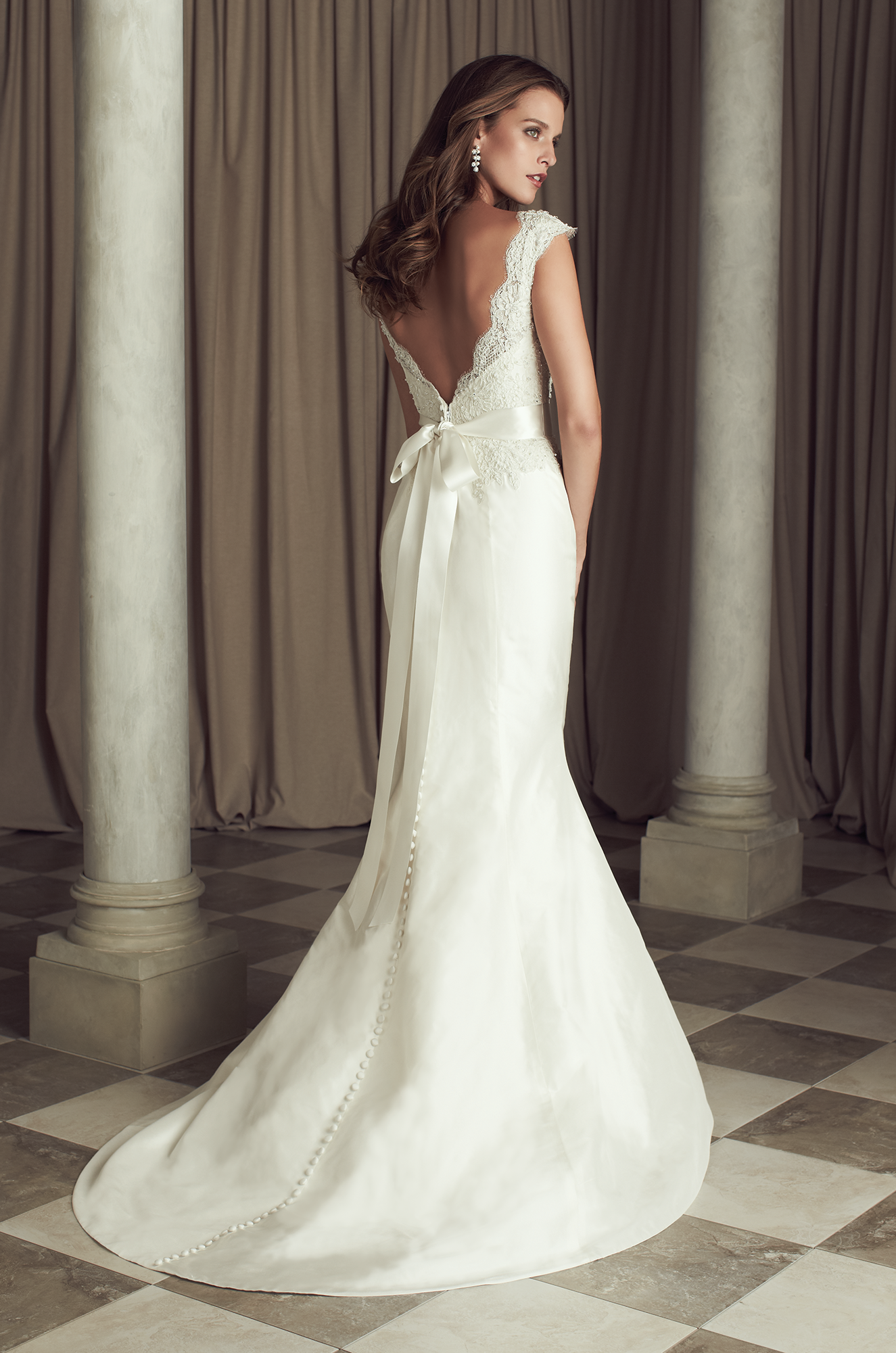 Paloma Re-embroidered Lace and Silk Dupioni Wedding Dress. V-neck beaded lace bodice with cap sleeves. Lace cascading onto skirt. Fit and flare Dupioni skirt with removable ribbon and flower detail at natural waist. Covered buttons over zipper to hem. Sweep Train. Style 4460. #PalomaBlanca #PalomaGown Paloma Blanca Wedding Gown