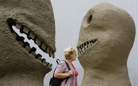 A woman walks past art sculptures in front of the main entrance of the Art 39 in Basel.