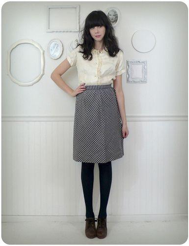 white designer shirt, neutral A line skirt, black hose, black mary janes